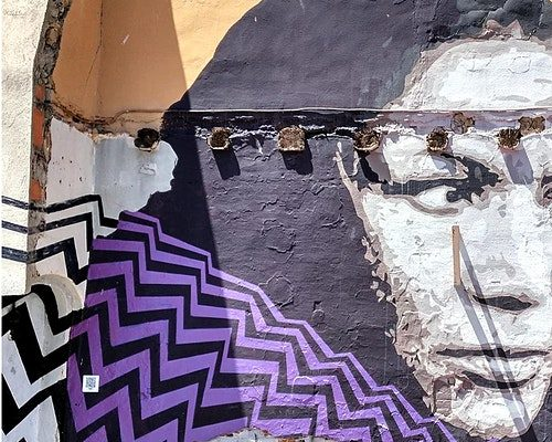 Street art featuring a woman's face on the side of a building with a colourful, geometric background