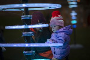 A small child in a bobble hat looks at a light sculpture with a bearded man