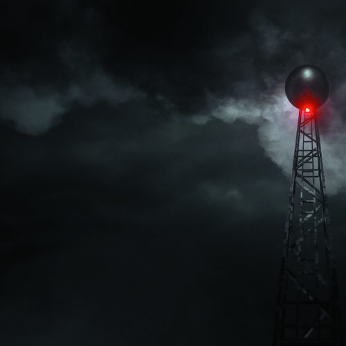A radio mast is surrounded by darkness and clouds. A single red light glows.