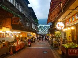 A bustling Asian street market at dusk, lit by warm orange street lighting.