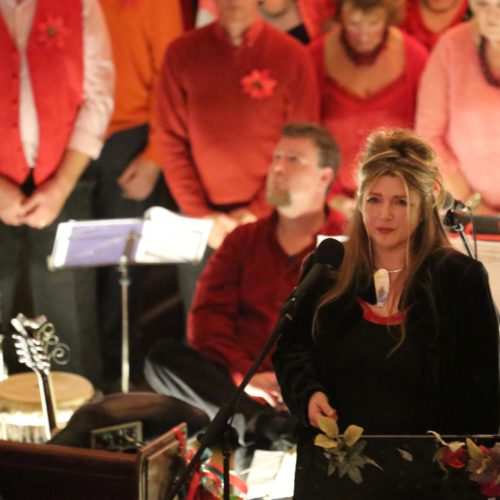 A woman dressed in black stands in front of a choir all dressed in red tones.