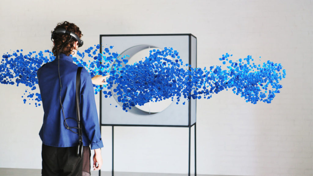 A person wearing virtual reality goggles reaches in front of them to touch a stream of blue bubbles flowing through a box with a hole in it.
