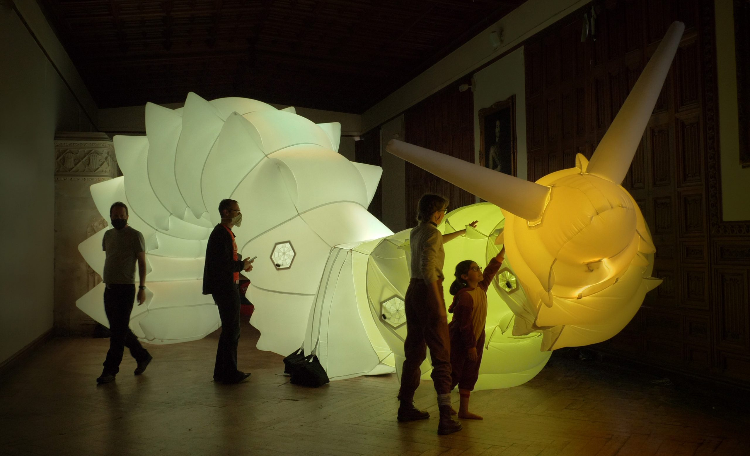 A large inflatable snail, lit from within with a young child reaching up to touch it.