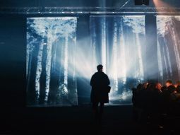 Projection of trees and man silohette standing in front of light
