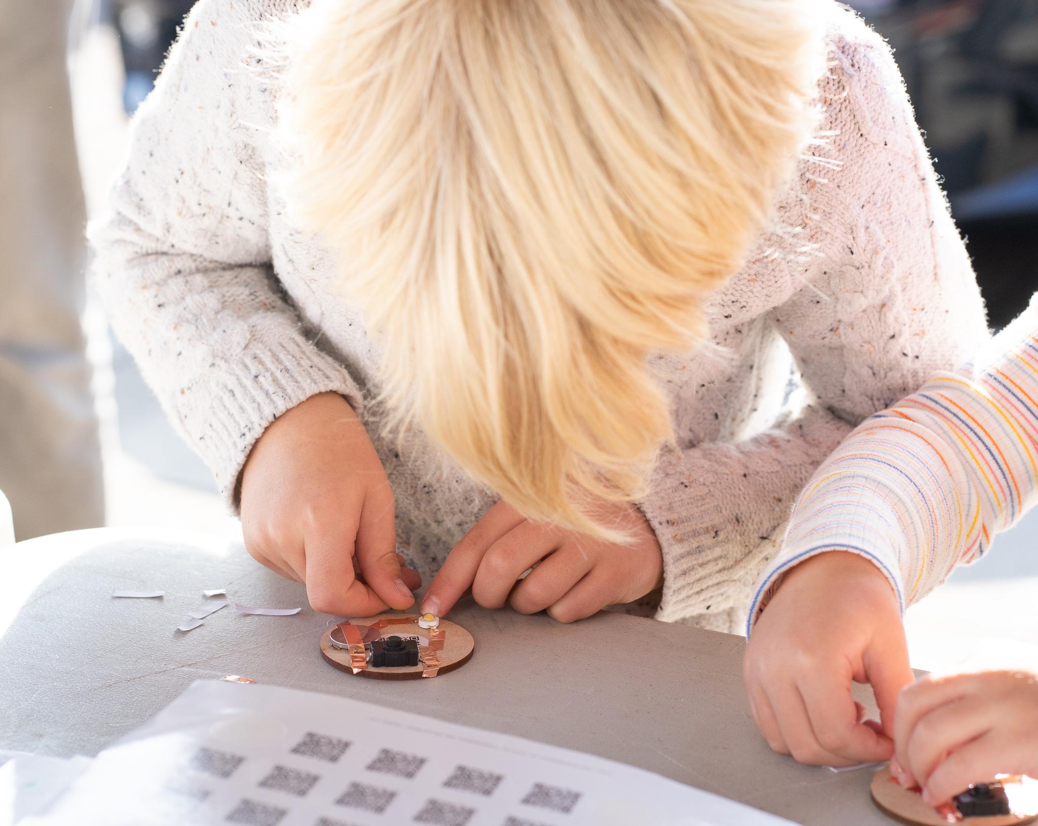 boy with blonde hair making a circuit badge in Lumo Workshop